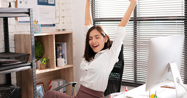 Employee stretching her back and raising her arms in her chair who is about to exercise during work break