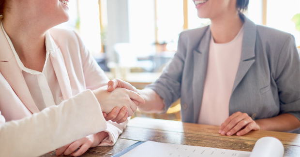 Hiring manager shakes hands with an applicant after a successful interview