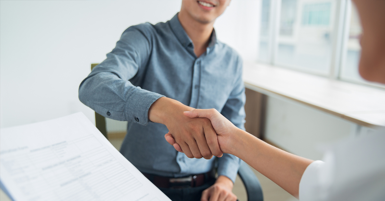 Applicant shakes hands with his employer after getting hired for a happy career
